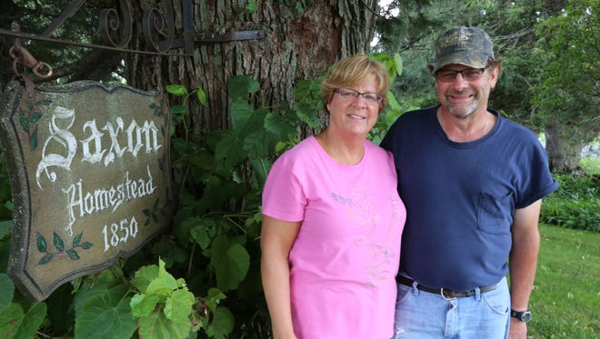 Liz and Karl Klessig stand next to the sign on their Cleveland farm.