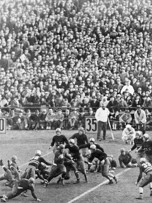 FILE - In this Nov. 26, 1932, file photo, part of a crowd of 80,000, watch Notre Dame running back Nicholas Lukats run for 4 yards against Army in the first half of a college football game at Yankee Stadium in New York. The Army-Notre Dame rivalry was one of the best of the 20th century.