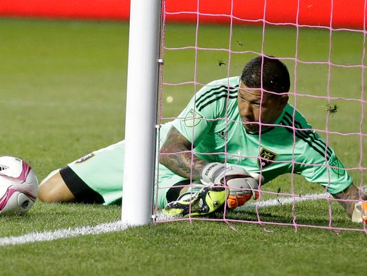 Real Salt Lake goalkeeper Nick Rimando (18) makes a save against the Portland Timbers in the first half during an MLS soccer game Wednesday, Oct. 14, 2015, in Sandy, Utah. (AP Photo/Rick Bowmer)