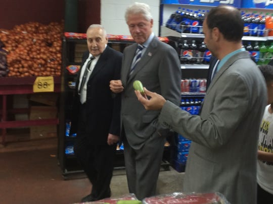 Bill Clinton tours Super Greenland Market in Dearborn on Nov. 6, 2016, looking at a vegetable known in Arabic as 'koussa.'