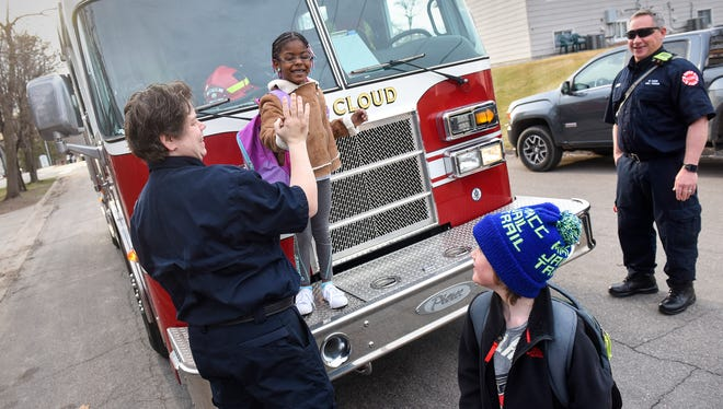 Firefighter Amy Spry and Talahi Community School kindergarten student Canyija Smith share a high-five before riding to school with student Aunders Anderson and firefighter Randy Giles Tuesday, April 24, in St. Cloud.