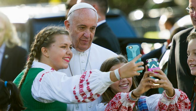 Children of parents who work at the Lithuanian Embassy take selfies with Pope Francis as he departs the Apostolic Nunciature, the Vatican's diplomatic mission in Washington, D.C., on Sept. 23, 2015.