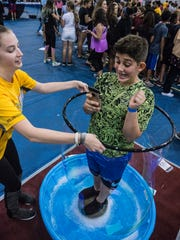 Gevon Hannawa, a student at Orchard Lake Middle School, is enclosed in a soap bubble created by Michigan Tech student Joellen Saugrich.