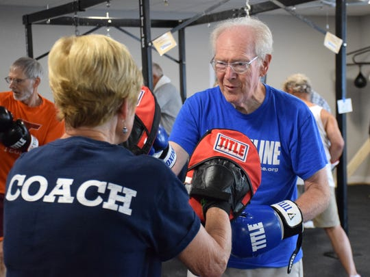 Participant Wayne Gibson hits the boxing mitts held