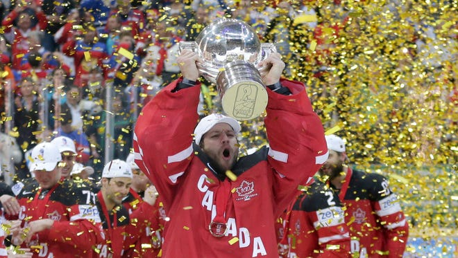 Canada's goalkeeper Mike Smith lifts the trophy after his team defeated Russia in the Hockey World Championships gold medal match in Prague, Czech Republic, Sunday, May 17, 2015.