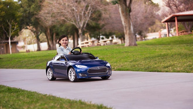 A girl gets behind the wheel of a sporty blue Tesla Model S for kids from Radio Flyer and takes it for a drive.