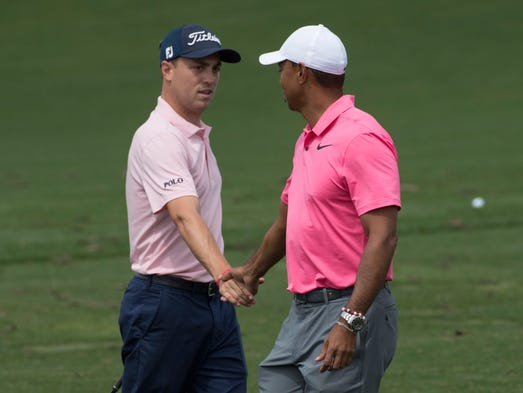 Justin Thomas shakes hands with Tiger Woods prior to