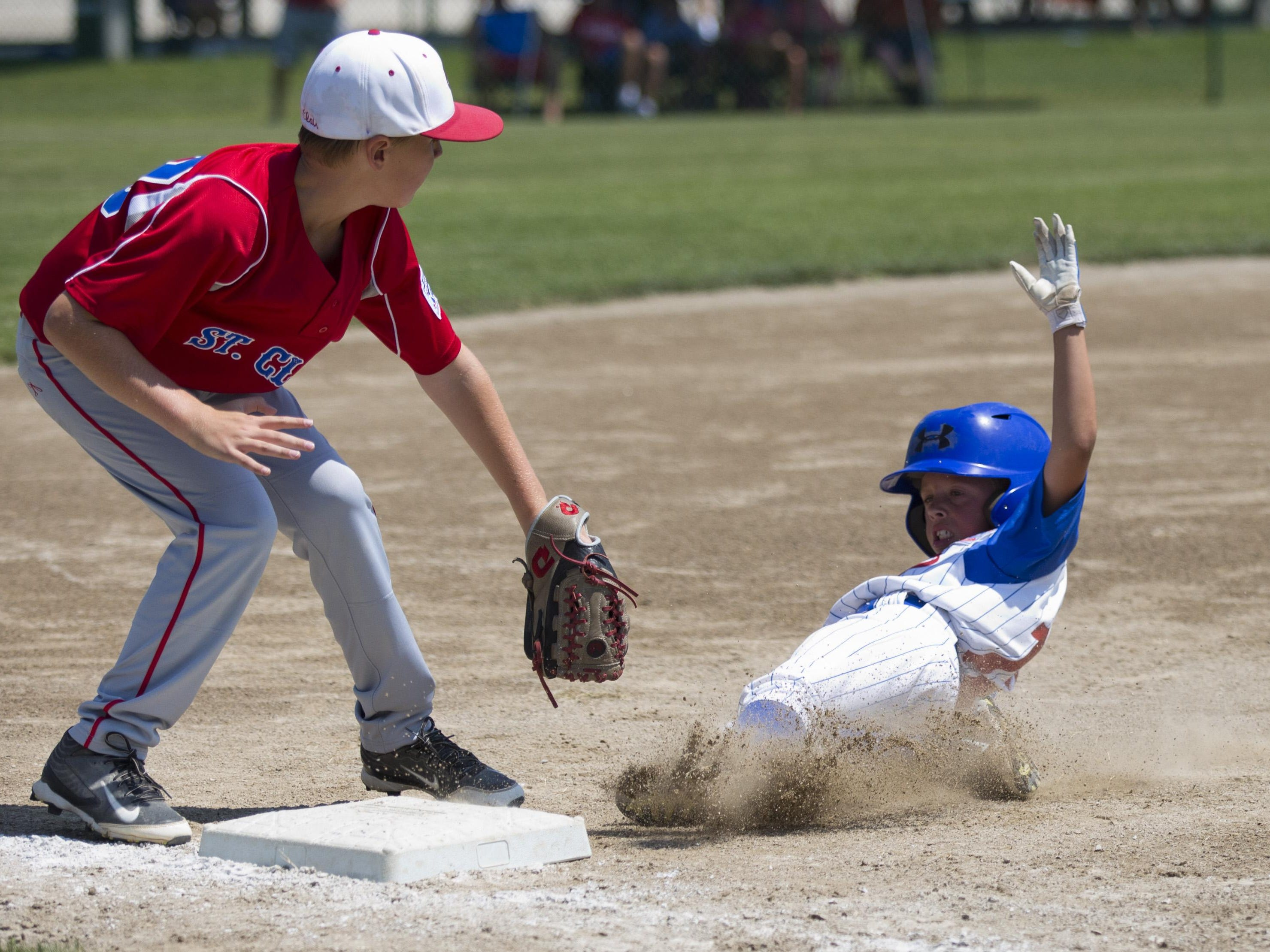 Carter Hurlburt makes a tag at third during a 10-and-under state semifinal baseball game Tuesday, July 28, 2015 in St. Clair.