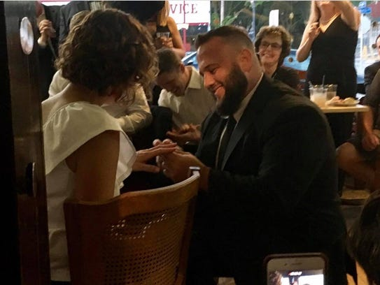 Joey Carioti slips an engagement ring onto Kristen
