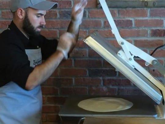 Tim Goff, co-owner of 3 Pepper Burrito Co., takes fresh tortilla dough and presses it into a 12-inch tortilla.