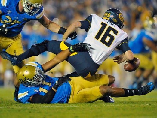 UCLA Bruins linebacker Anthony Barr (11) brings down California Golden Bears quarterback Jared Goff (16) during the first half at the Rose Bowl.