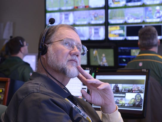 Al Gutowski watches a monitor in the Green Bay Packers