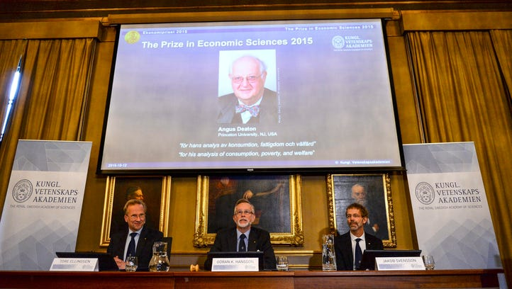A picture of Angus Deaton, winner of the Nobel Prize in economics, is seen on a screen as members of the Royal Swedish Academy of Sciences announce the award.