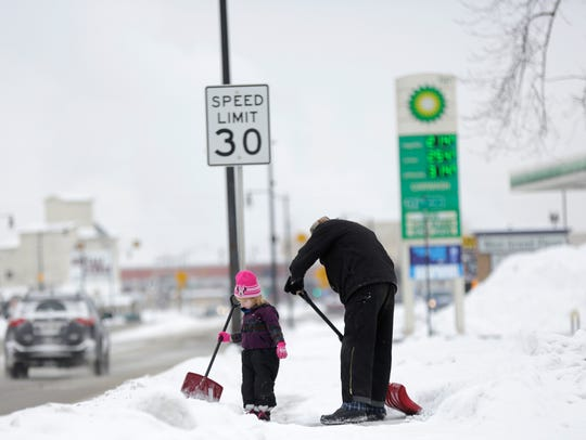 Nevaeh Colloway, 3, helps her father Keith shovel the