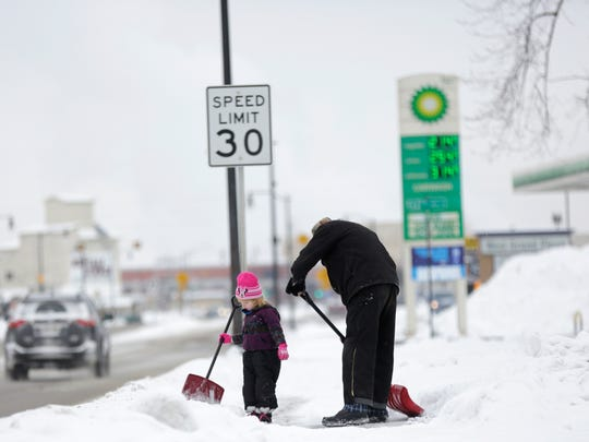 Nevaeh Colloway, 3, helps her father Keith shovel the sidewalk in front of their home along Grand Avenue in Wisconsin Rapids ahead of a winter weather advisory for the entire region where more than a foot of snow is expected, Friday December 16, 2016.