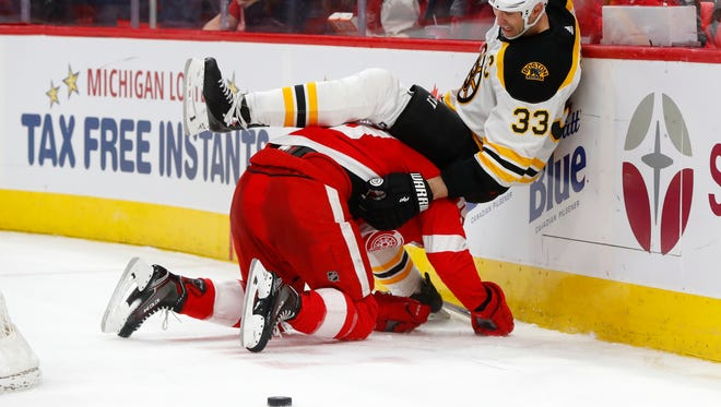 Boston Bruins defenseman Zdeno Chara (33) falls over Detroit Red Wings right wing Anthony Mantha during the second period of an NHL hockey game Tuesday, Feb. 6, 2018, in Detroit.