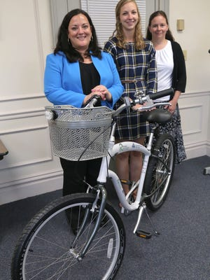 Mary Frankenfield, deputy director of the Richland County Public Library, Ellen Claiborne of Richland Public Health and Molly Ernst, recourses administrator for the library stand next to cruiser bicycle that soon can be rented from the library.