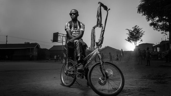 "Joel Nsadha's winning photo with the caption: ""Bwengye lives in a slum called Kamwokya in Kampala, Uganda's capital city. He cherishes his bicycle more than anything and brings it to this playground in the slum every evening, where he watches kids playing soccer."""