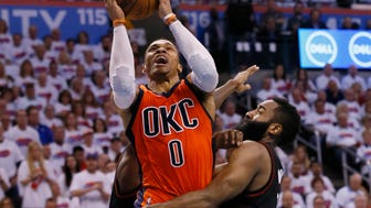 FILE - In this April 23, 2017 file photo, Oklahoma City Thunder guard Russell Westbrook (0) shoots between Houston Rockets guard Patrick Beverley, rear, and guard James Harden, right, in the fourth quarter of Game 4 of a first-round NBA basketball playoff series in Oklahoma City. Westbrook will join Houston's James Harden and San Antonio's Kawhi Leonard as finalists for the league's MVP award. The winner will be announced Monday, June 26, at the inaugural NBA Awards show. (AP Photo/Sue Ogrocki, File)