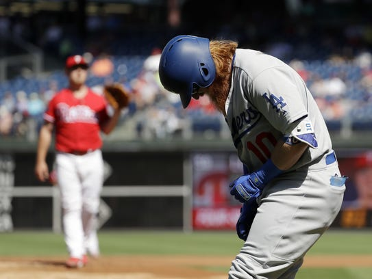 Justin Turner, right, reacts after getting hit by a