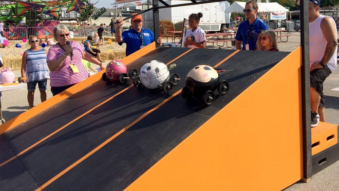 """Entries dubbed (from left) """"Pink Princess,"""" """"Melting Dalmatians"""" and """"Minnie Mouse"""" compete in the Pumpkin Derby at Harvest Fest at State Fair Park."""