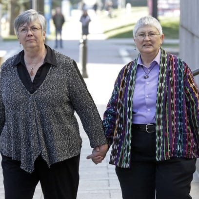 In this March 12, 2014, file photo plaintiffs JoNell Evans, left, and Stacia Ireland walk together at the Frank E. Moss United States Courthouse in Salt Lake City after a federal judge heard arguments from four same-sex couples suing Utah over its decision to stop granting benefits to newly married gay couples.