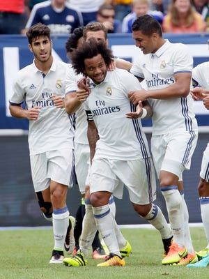 Marcelo is surrounded by teammates after scoring one of his two first-half goals.