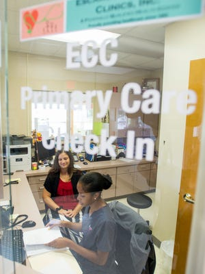 Financial counselor Jennifer Large, left, looks on as patient access representative Jazmine Jones goes over paperwork at the front desk of the new Escambia Community Clinic in Century on Wednesday, Aug. 9, 2017.  The clinic is sharing the building with the previously established Lakeview Center in Century.
