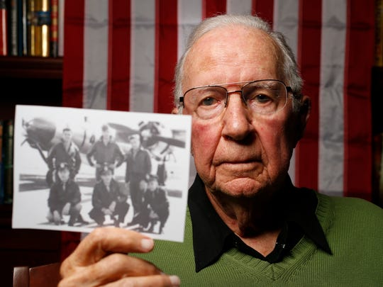 World War II veteran Cyrus Kirk holds up a photo of him and his Army Air Corps squad members Wednesday, Nov. 5, 2015, at the Deerfield retirement community in Urbandale.