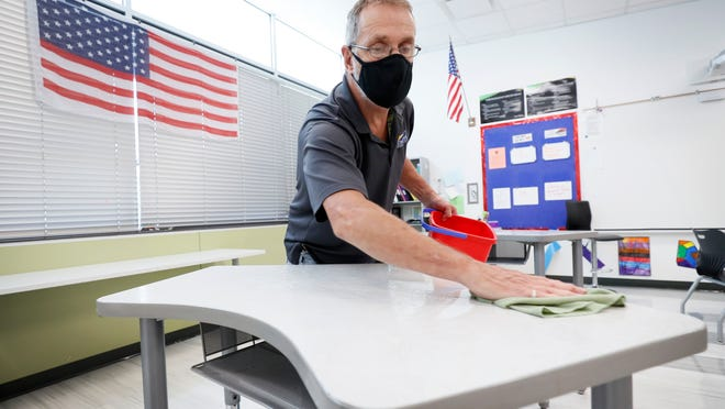Custodian Doug Blackmer cleans a desk in a classroom at the Jesse Franklin Taylor Education Center in Des Moines, Iowa.