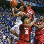 Kentucky's Tyler Ulis tries to split through Arkansas' Moses Kingsley in the second half during the Wildcats' 84-67 win Saturday over Arkansas. Ulis had 14 points. By Matt Stone, The Courier-Journal February 28, 2015