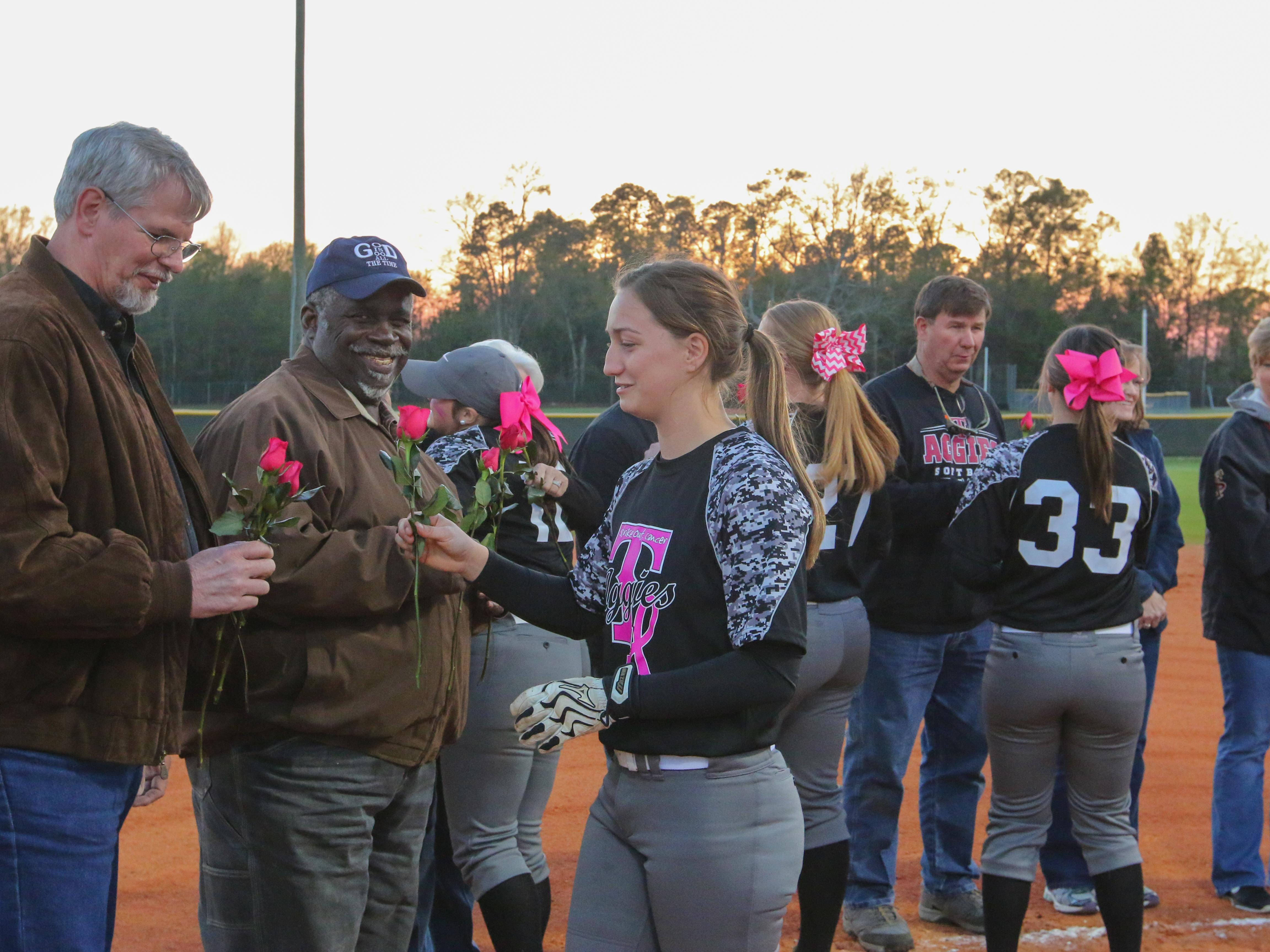 Tate's softball team presents roses to cancer survivors in attendance before the start of the 7th Annual Strike Out Cancer benefit softball game at Tate Monday night. The event helps raise thousands of dollars for the American Cancer Society.