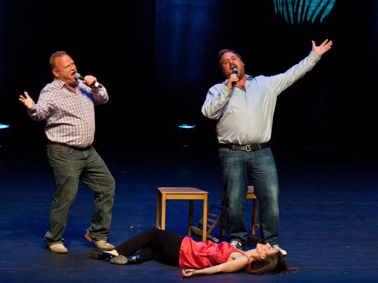 Larry Joe Campbell and Jim Belushi perform a skit in front of a crowd, while Megan Grano lies down.