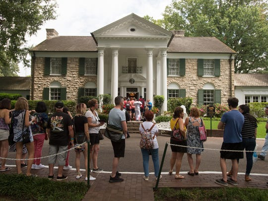 Fans wait in line outside Graceland, Elvis Presley's Memphis home, in Memphis, Tenn. Elvis Presley's Graceland says it will reopen Thursday, after it shut down tours and exhibits due to the new coronavirus outbreak.