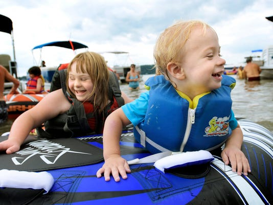 Siblings Aubrey, 9, and Kade Pace-Sensenig, 1, of Abbottstown, Adams County, are spun on a float while boating on the Susquehanna River during the Susquehanna Yacht Club's Four Diamonds Day event Saturday, August 8, 2015. The club annually holds the event to give families of child cancer patients a day on the water as well as lunch and prizes. Aubrey battled acute myeloid leukemia and has been in remission for 8 years. About 20 families attended this year. Bill Kalina - bkalina@yorkdispatch.com