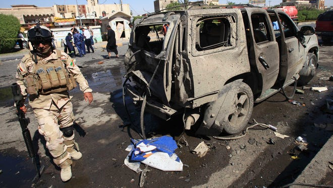 An Iraqi soldier inspects the site of a car bomb attack in Basra, 340 miles southeast of Baghdad, Iraq, on Oct. 13, 2013.