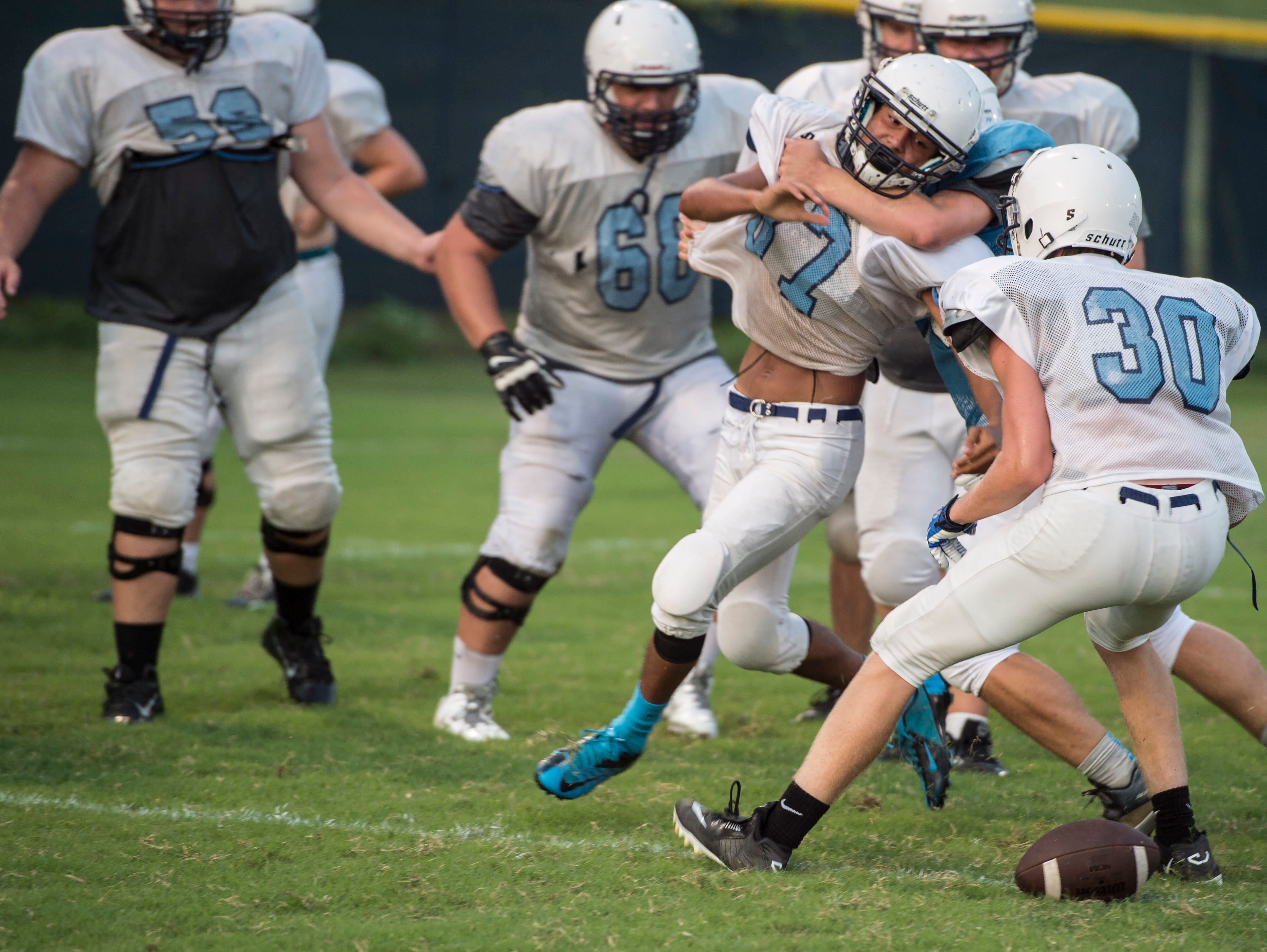 Centennial football players do the savage drill where on player has to get the ball and two players try to keep him from getting it during Centennials HS first day of football practice onTuesday July 28, 2015, in Franklin