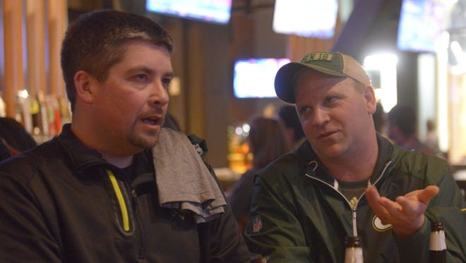 Hutch Ruggles of Eau Claire, right, makes a point to Quincy Devine of Withee on Thursday at 1919 Kitchen & Tap while waiting for the Green Bay Packers to draft.