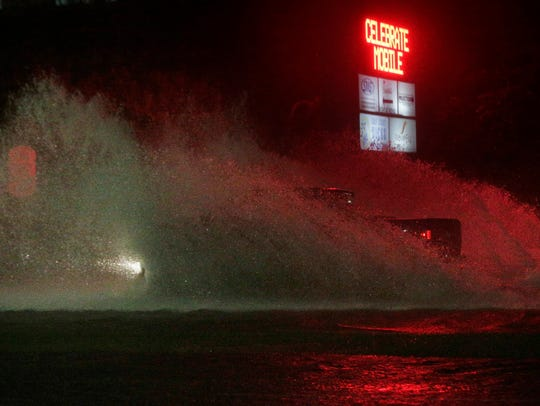 A large truck drives through a flooded Water St. in