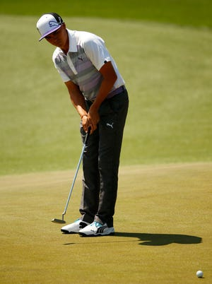 Rickie Fowler putts on the 14th green during the third round of the 2014 The Masters golf tournament at Augusta National Golf Club.