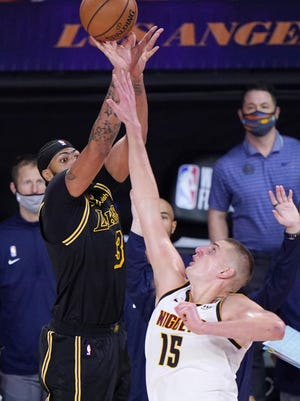 Los Angeles Lakers' Anthony Davis (3) shoots a 3-point basket over Denver Nuggets' Nikola Jokic (15) Sunday in Lake Buena Vista, Fla.