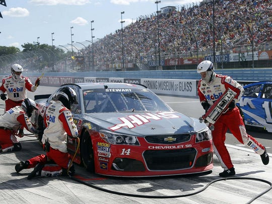 Tony Stewart  makes a pit stop in front of packed grandstands