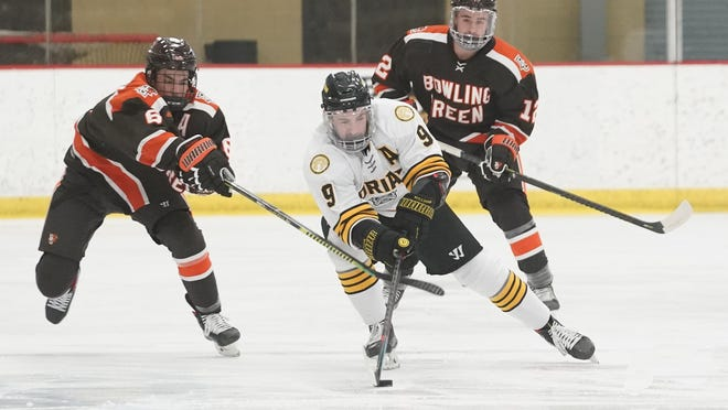 Adrian College forward Sam Ruffin (9) controls the puck as Bowling Green's Alex Barber (6) and Gavin Gould (12) pursue him in the first period of Saturday night's contest at Arrington Ice Arena. The Falcons improved to 2-0 on the season with a 5-0 victory over the Bulldogs.