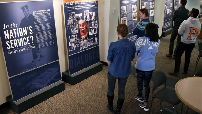 Princeton University students walk through an exhibit titled, 'In the Nation's Service? Woodrow Wilson Revisited,' Sunday at the Woodrow Wilson School of Public and International Affairs in Princeton.