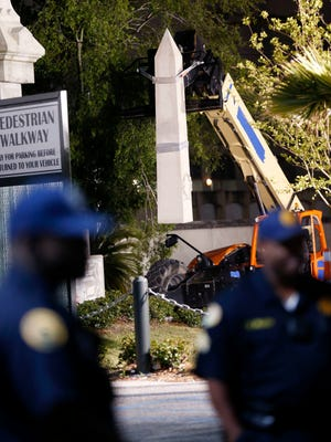 Workers dismantle the Liberty Place monument Monday, April 24, 2017, which commemorates whites who tried to topple a biracial post-Civil War government, in New Orleans. It was removed overnight in an attempt to avoid disruption from supporters who want the monuments to stay.