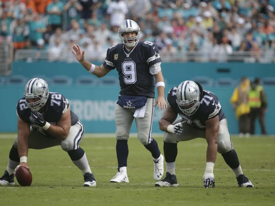Dallas Cowboys quarterback Tony Romo (9) calls a play during the first half of an NFL football game against the Miami Dolphins, Sunday, Nov. 22, 2015, in Miami Gardens, Fla. To the right is offensive guard La'el Collins (71) and left center Travis Frederick (72) (AP Photo/Wilfredo Lee)