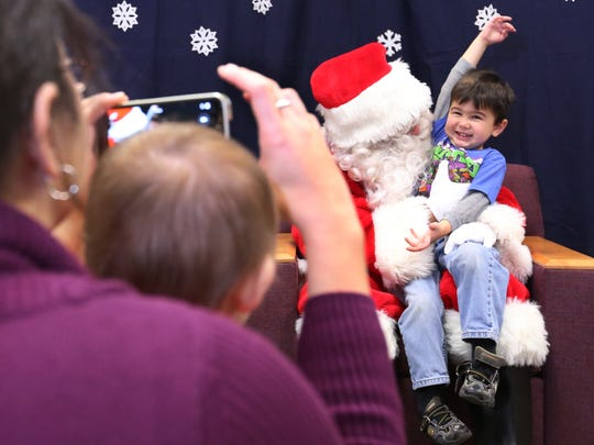 Mylan Kohler, of Manitowoc, takes photographs of her son, Zachory, meeting Santa Claus at the Manitowoc Public Library's Saturday Morning with Santa event in December 2015.