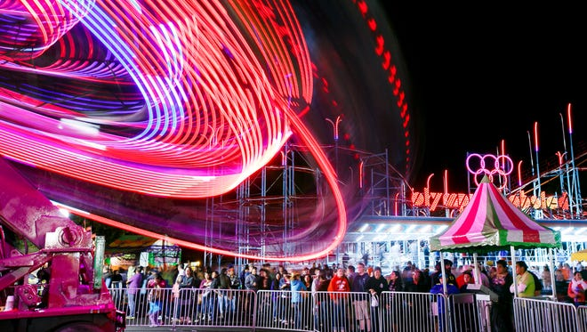 Crowds watch as the Star Trooper ride spins at the Oregon State Fair on Saturday, Sept. 3, 2016. The fair featured 47 carnival rides this year, operated by new contractor Rainier Amusements.