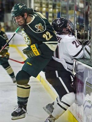 Vermont's Brady Shaw, left, checks Nebraska-Omaha's Jake Guentzel into the boards in Burlington on Friday.