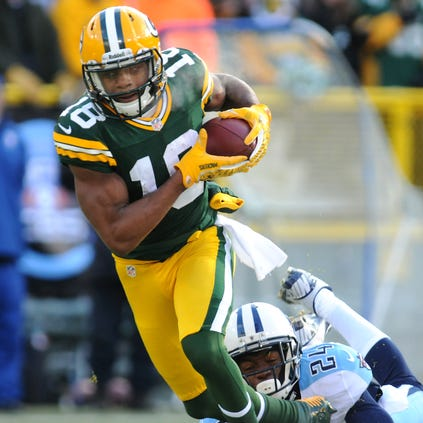 Packers wide receiver Randall Cobb slips away from Titans cornerback Coty Sensabaugh.